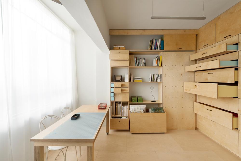 Amenajarea unui studio de lucru de 14 mp: rafturile, delimitările şi fronturile mobilei sunt din placaj.